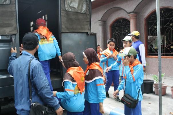 siswa mulai naik mobil polisi yang siap mengantar, nampak ustadz tetap mendampingi