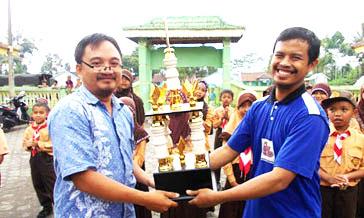kepala sekolah MI Al-Ikhlas menerima hadiah piala juara umum dengan 2 emas dan 1 perunggu