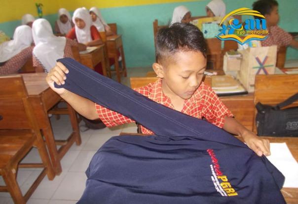 salah satu siswa melipat baju. baru belajar melipat karena menurutnya tidak pernah melakukan di rumahnya